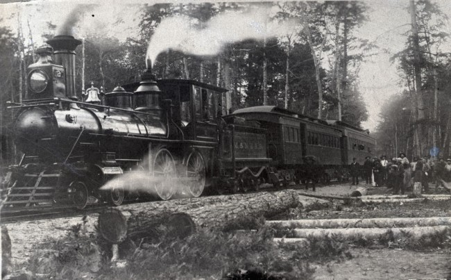 Historical photo of Manistee North Eastern Rail Road Locomotive as seen at a logging camp with workers standing in the background and cut trees in the foreground as the train goes by