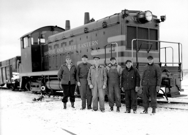 Historical photo of Manistee and NOrth Eastern Rail Road Workers standing in front of a locomotive in the winter with snow on the ground