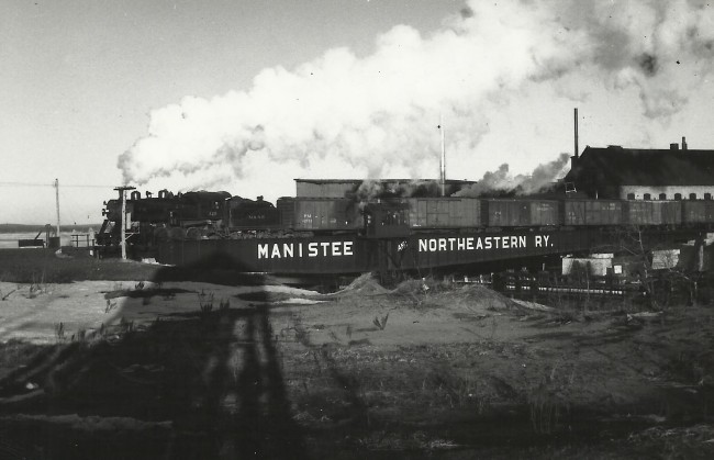 Historical Photo of a trail going over a  Railroad Bridge that is labeled Manistee and Northeastern Rail Road