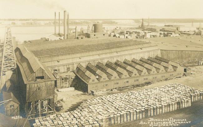 Historical photo of the Buckley - Douglas Mill with piles of lumber stacked in neat rows around their huge building on Manistee Lake