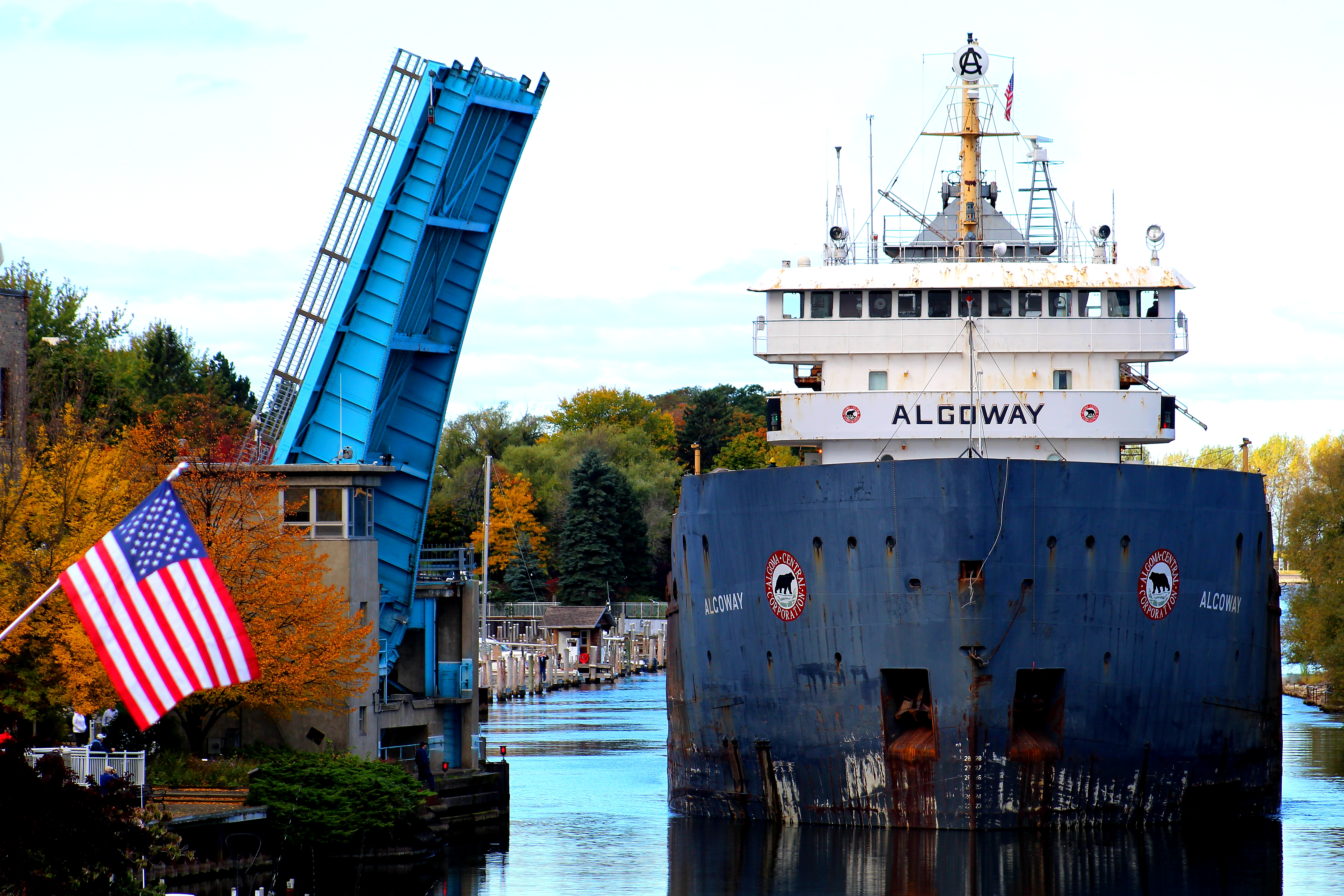 Freighter Algoway in the Mansitee River Channel at Maple Street Bridge with a US Flag in the foreground of the picture on a fall day when the leaves are changing on the trees in the background