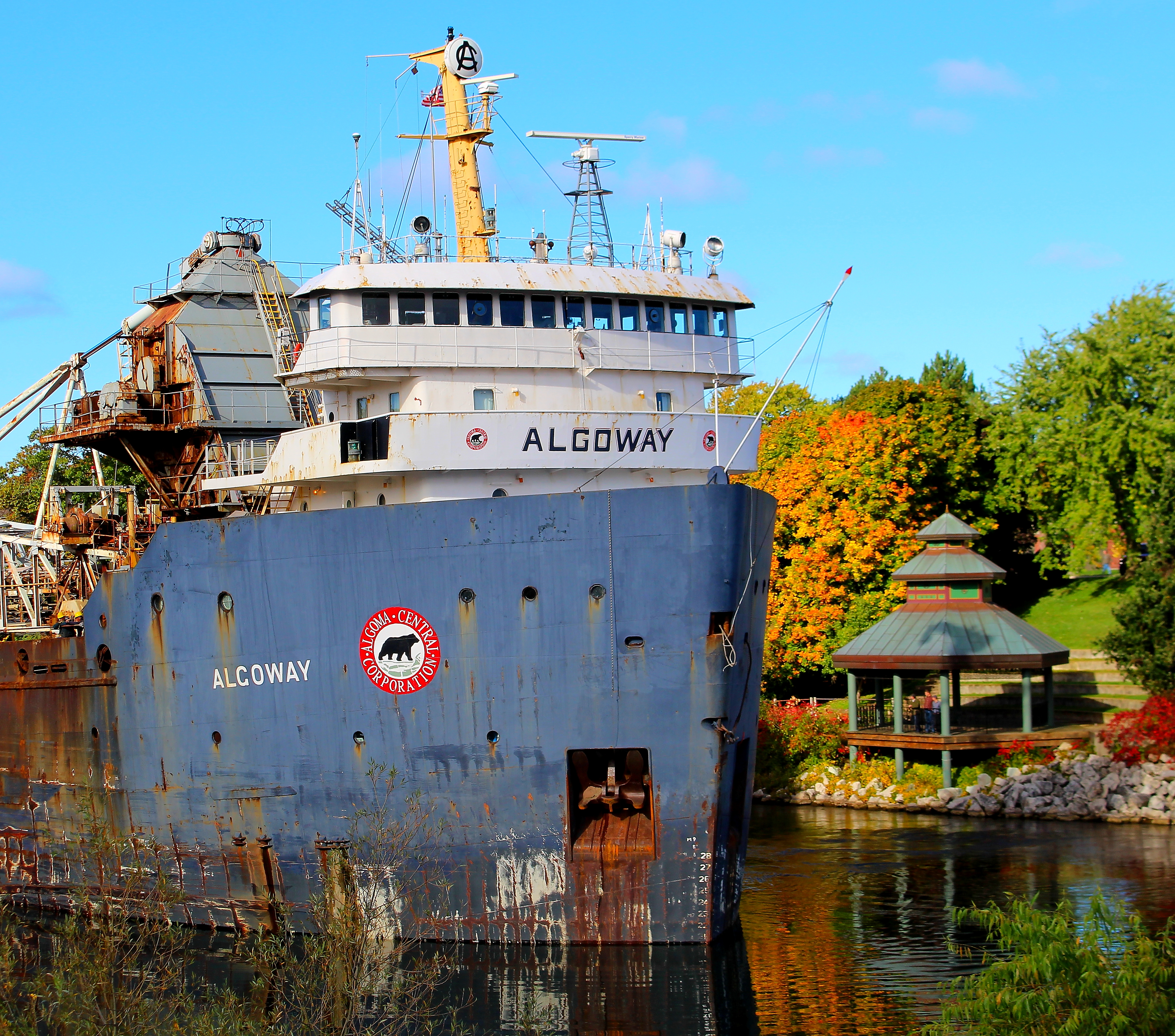Freighter Algoway in the Manistee River Channel with the Bandshell in the background as the leaves are changing on the trees in Autumn