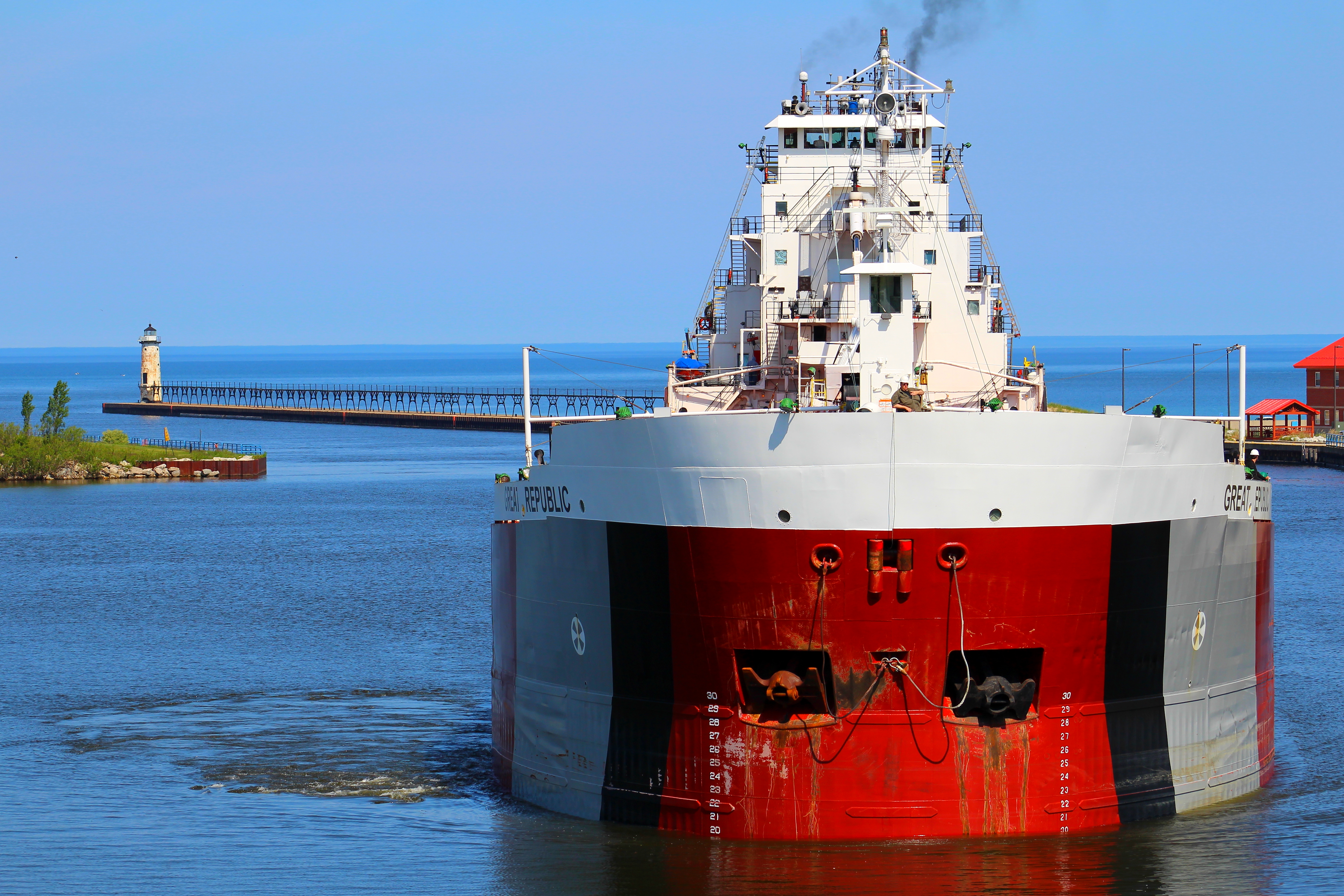 Freighter Great Republic entering the Manistee River Channel with the Fifth Avenue Lighthouse in the background