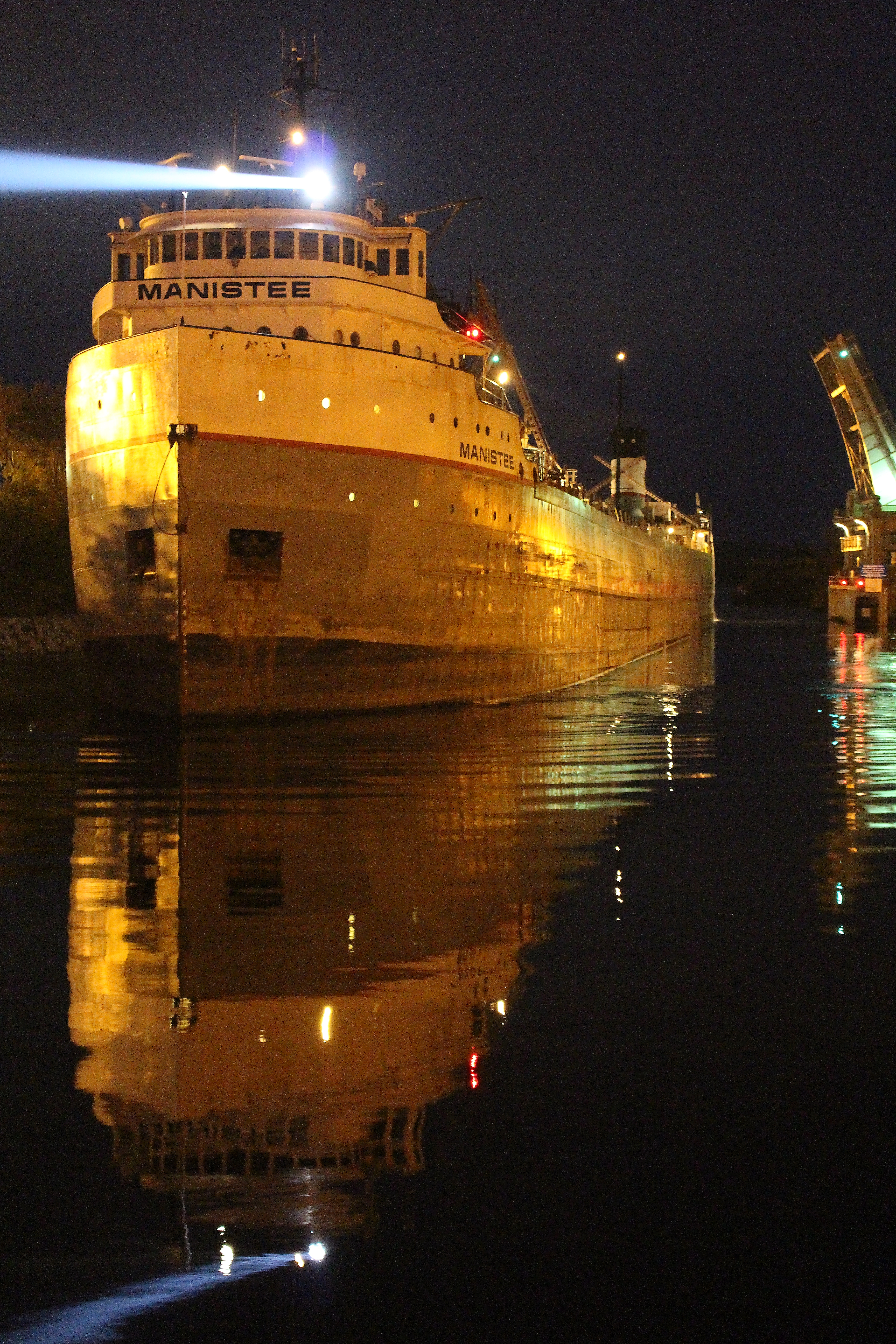 The Freighter Manistee at night as it navigates through the  US 31 Bridge in the Manistee River Channel