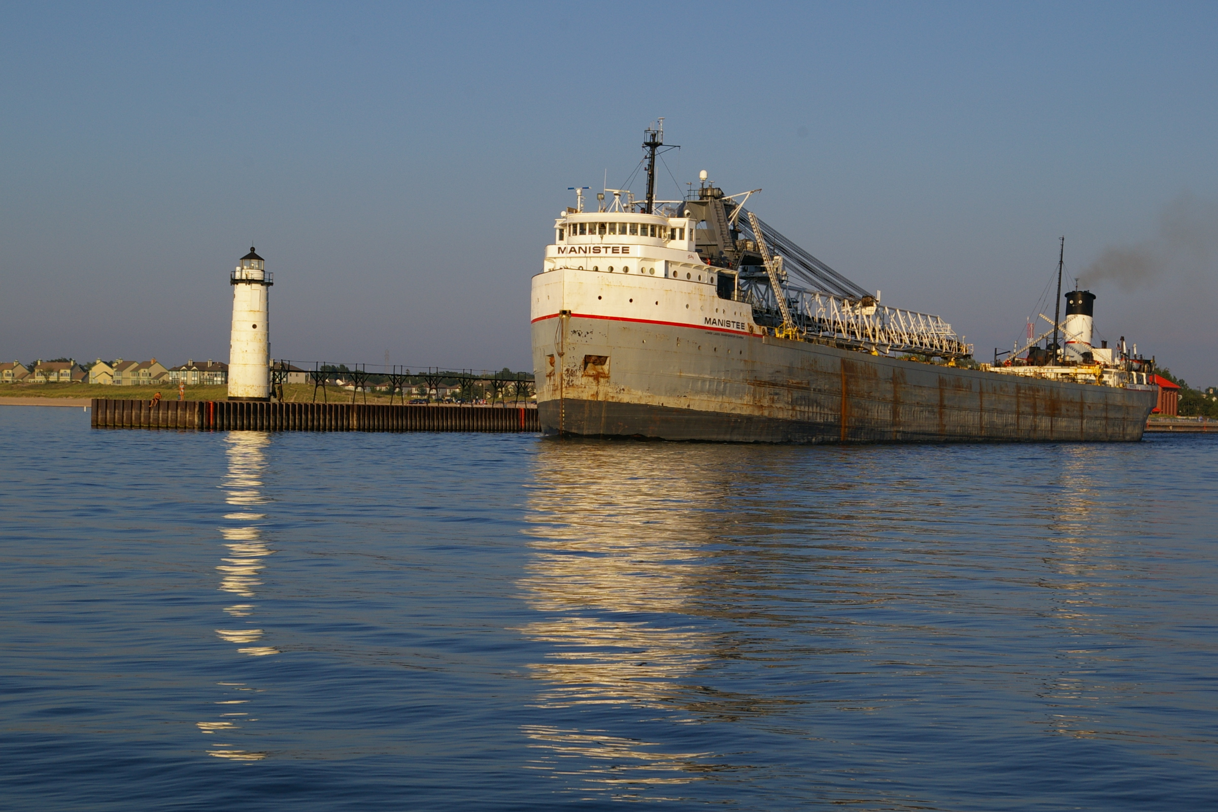 Great Lakes Freighter Manistee exiting the Harbor next to the Fifth Avenue Lighthouse  as seen from Lake Michigan