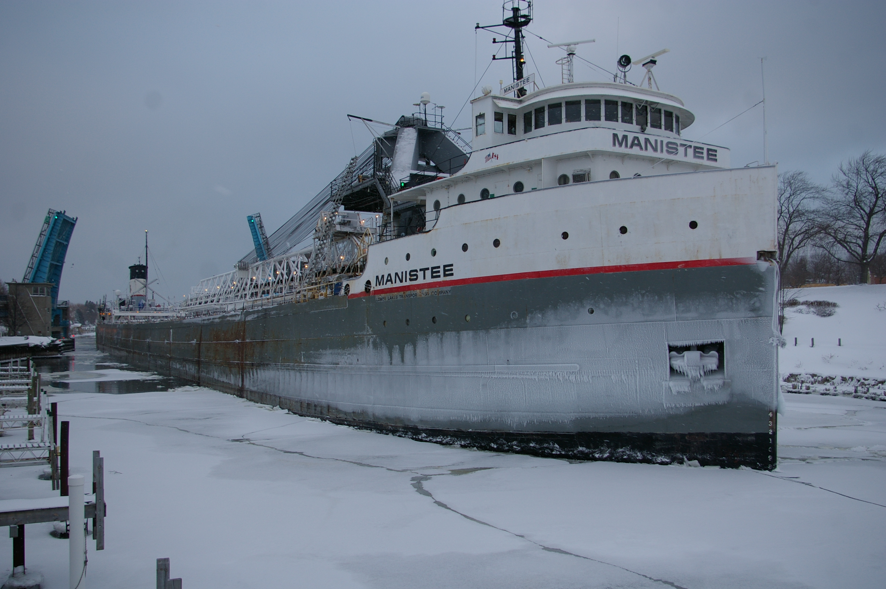 Great Lakes Freighter Manistee is navigating the frozen water in the Manistee River Channel in Winter