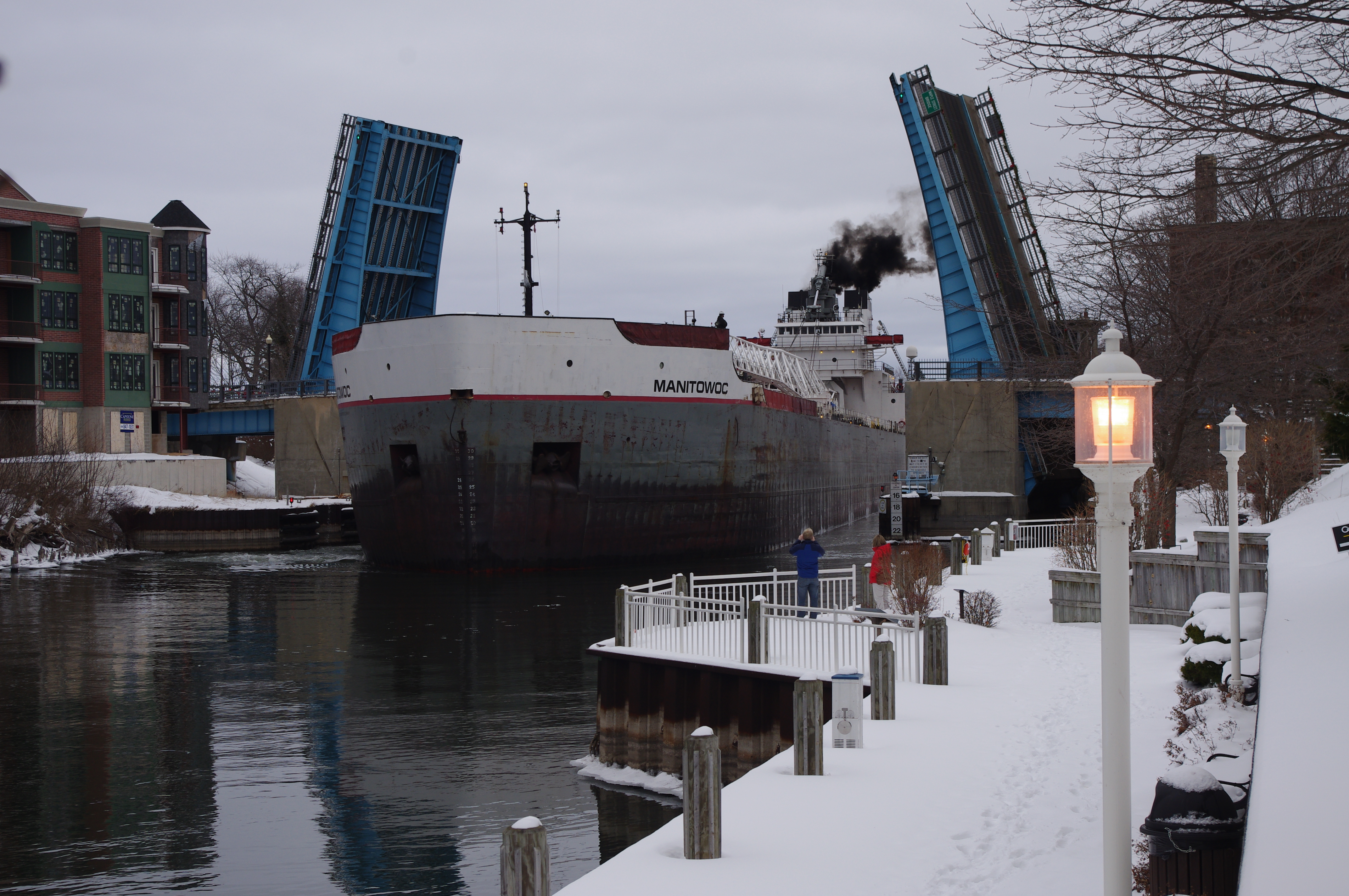Snow is seen on the riverwalk in the foreground of this photo of Great Lakes Freighter Manitowoc as it goes through the Maple Street Bridge in winter