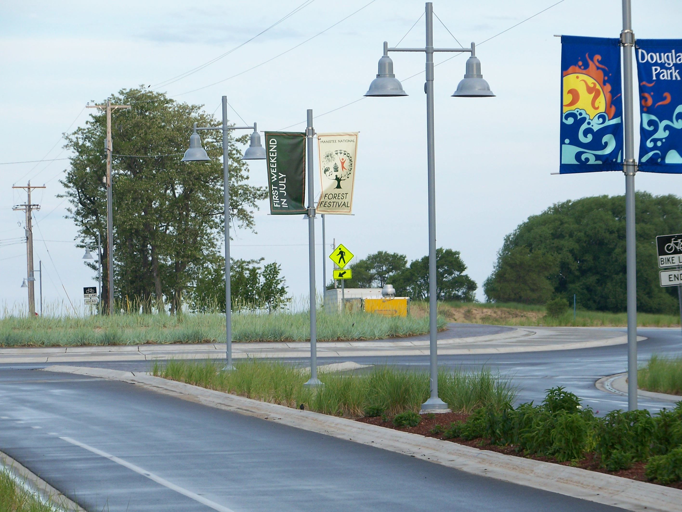 The entrance to Douglas park has a roundabout that is accessed from First Street where there is a landscaped boulevard that includes banners, lights, sidewalks and a bike lane