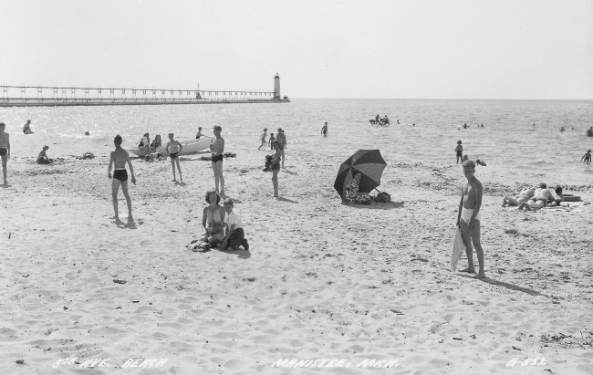 Black and white photo of Fifth Avenue beach that is undated showing people on the beach, an umbrella and people swimming in Lake Michigan, the Fifth Avenue Lighthouse and catwalk are in the background