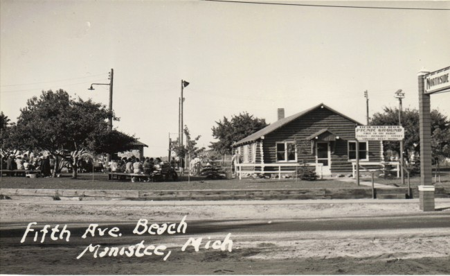 Black and white photo of the Log constructed former Northisde Improvement Association building at Fifth Avenue Beach,