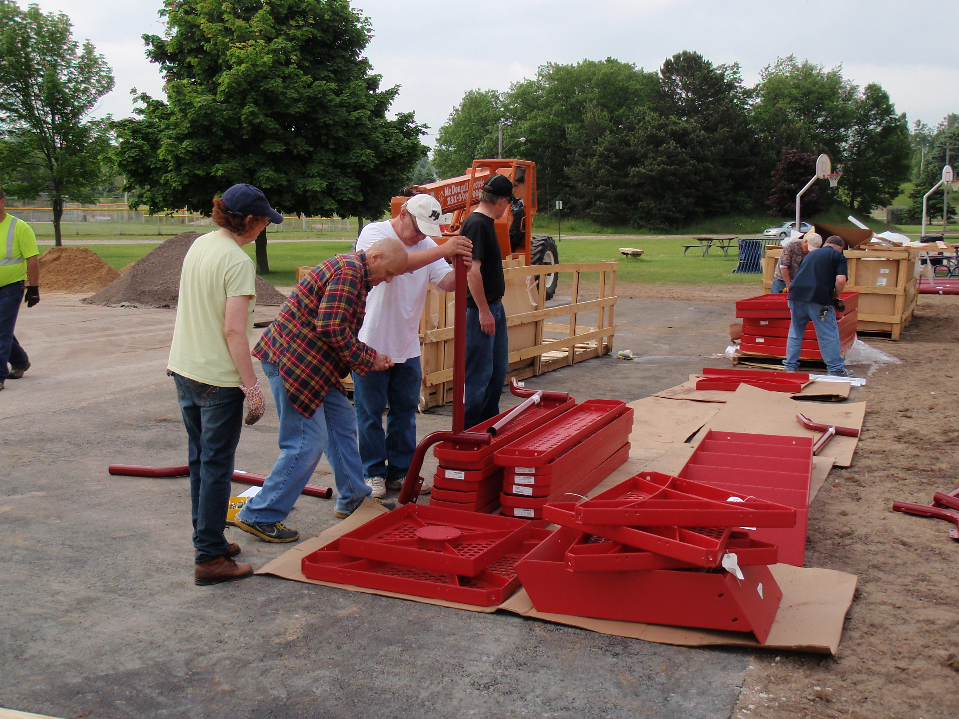 Workers are unpacking the playground equipment for the community build of Rocket Park