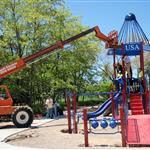 A lift is being used to install the top of the large rocket slide that is the focal point of Rocket Park volunteers are seen working on the community build of the park