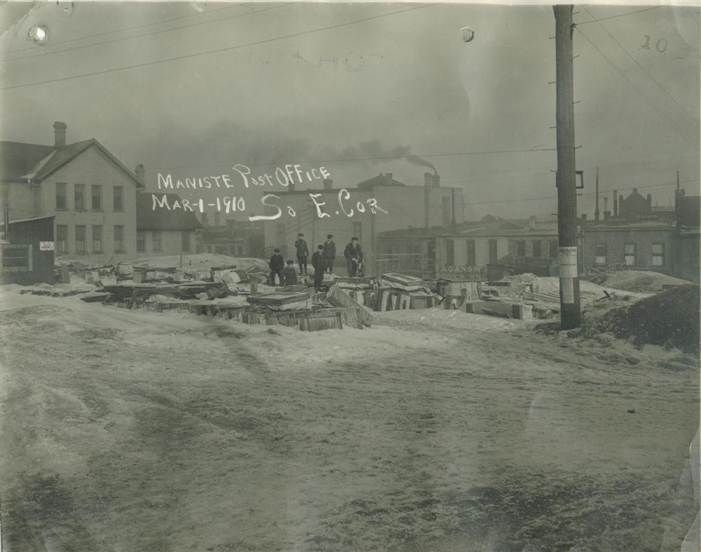 Historical photo taken in March 1910 showing the post office construction site covered in snow with a group of children and a dog in the photo taken from the southeast corner overlooking the site