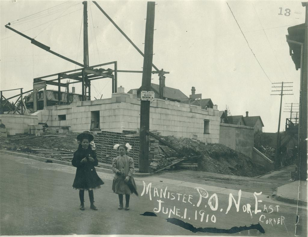 Two young girls one with a hat and the other with bows in her hair have their photo taken in front of the construction site of the post office showing the lower layer of stone in place taken from the northeast corner overlooking the site