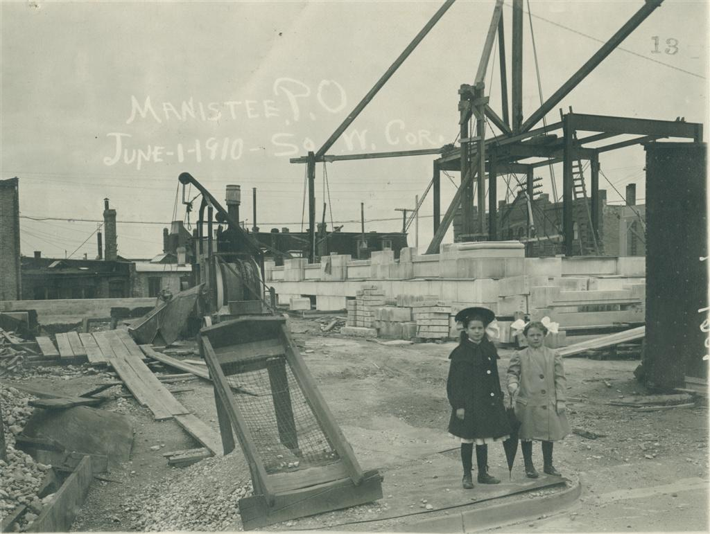 Post Office construction site photo taken in June 1910 with two young girls in the foreground of the photo one is wearing a hat the other has bows in her hair and is holding an umbrella with the base layer of limestone in place