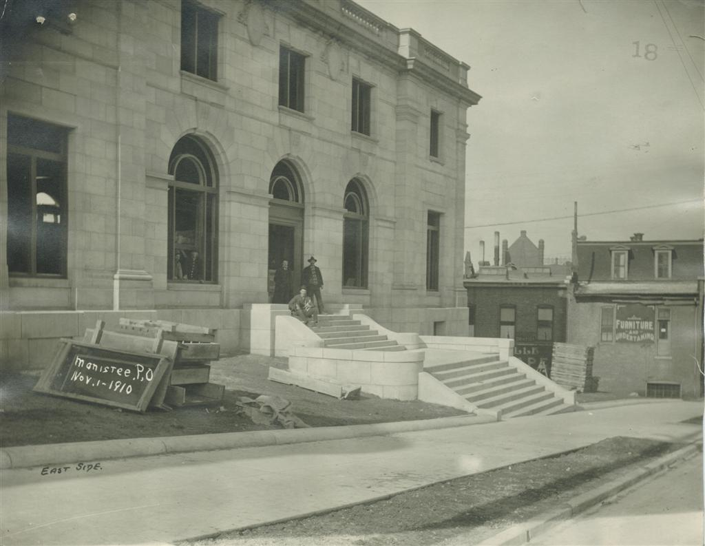 Historical photo from November 1910 shows the stairway for the Maple Street entrance in place railings, lights, windows and doors have not been installed three men are at the top  of the stairway in the photo