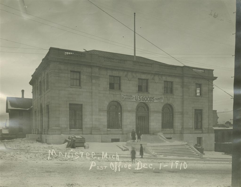 Photo taken December 1910 showing the post office as seen from Maple Street windows and doors have been installed and a banner hangs on the building that reads