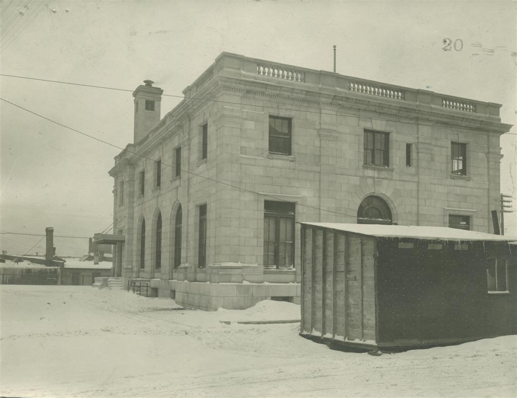 Exterior historical photo showing the south west corner of the Post Office in winter with snow on the ground and a tool shed in the foreground