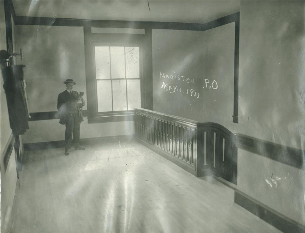 Historical photo taken in May 1911 showing the  second floor landing with the beautiful wooden stairway and railing  a man wearing a hat is in the photo holding a small dog