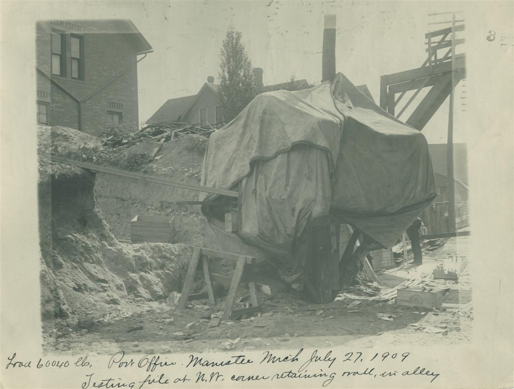 A tarp is draped over the footing test for the post office as seen from the alley