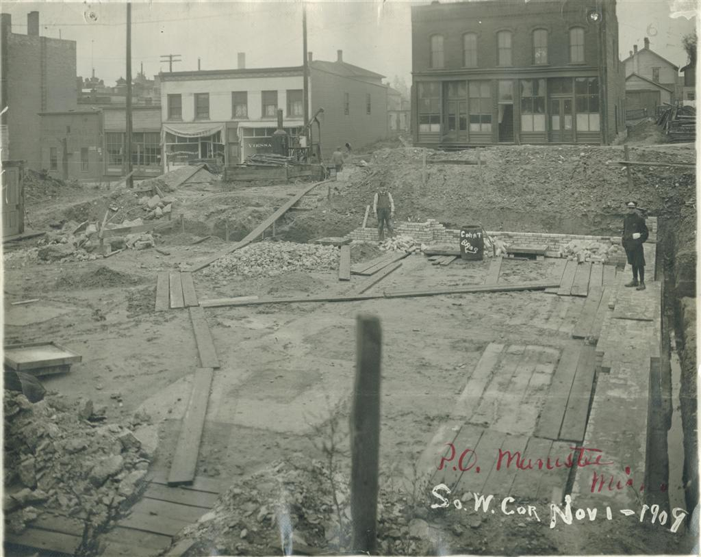 Base brickwork begins on the Southwest corner site includes equipment and wooden walkways used to access work site November 1909