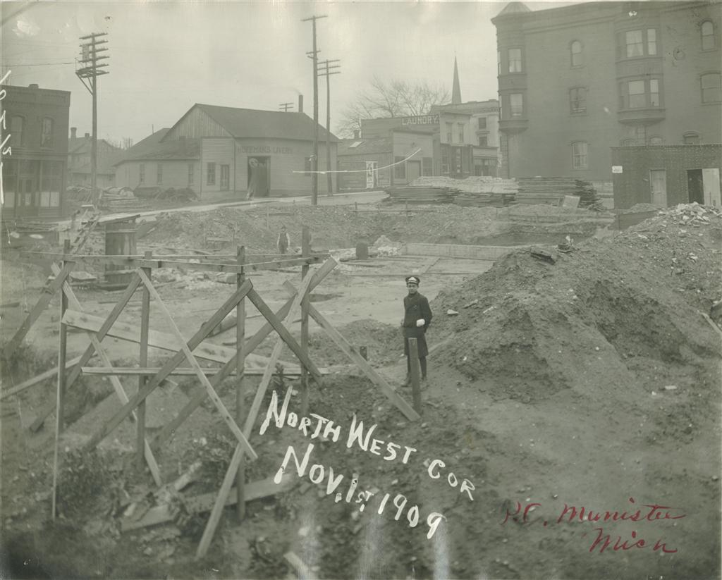 Southwest corner base brickwork is beginning with a view of the site taken from the northwest corner, a young man is shown wearing a hat and vintage clothing from 1909