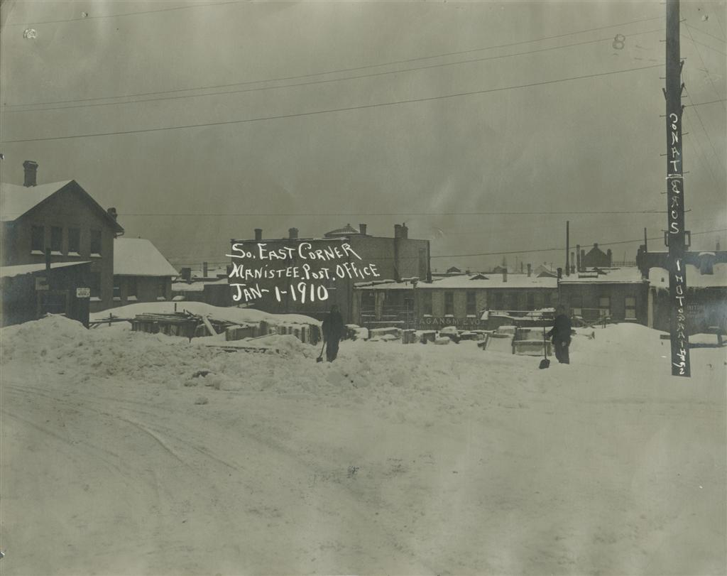 Two men are seen holding shovels standing in the snow of the site of the post office as seen on January 1, 1910