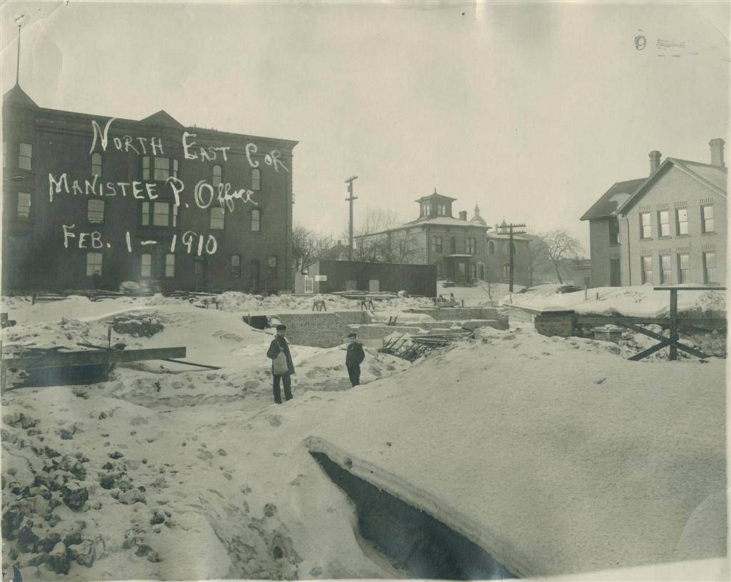 Historical photo of site of Post Office covered in snow with two children taken from the northeast corner overlooking the site