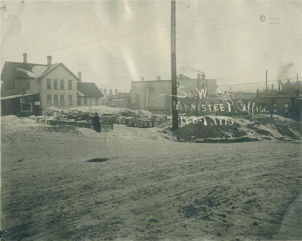 Historical photo of Post Office construction site taken in February 1910 showing the site with a child in the photo taken from the southwest corner
