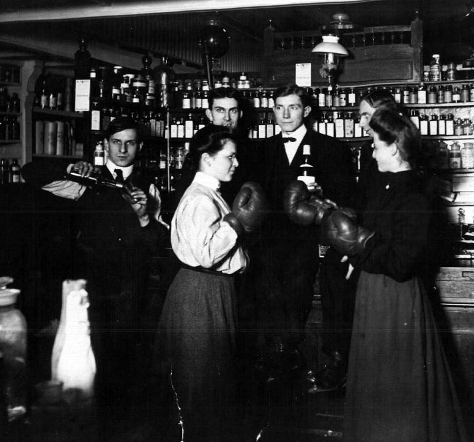 Historical photos of employees of AH Lyman Drug Co circa 1900 women are wearing boxing gloves and the gentlemen are sharing a drink