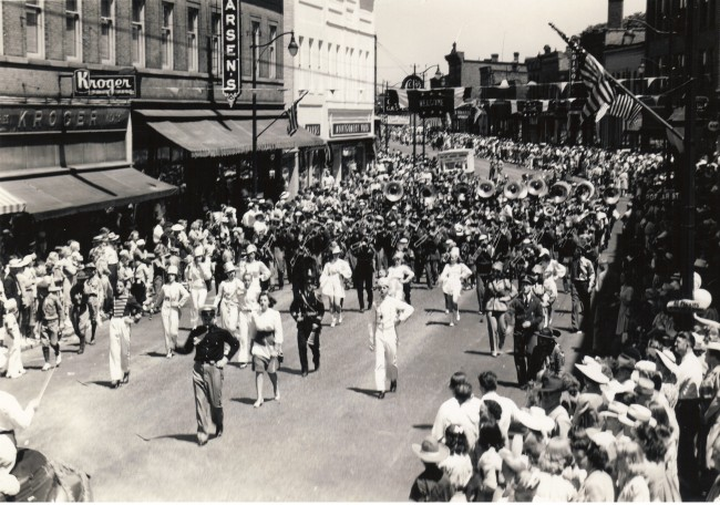 Black and white photo of a band marching down River Street with the sidewalks full of spectators