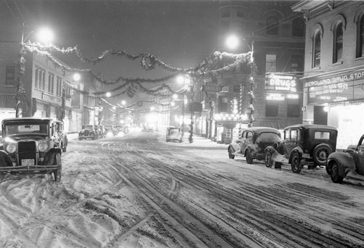 River Street Christmas c. 1930 with snow on the road a a light dusting of snow on vehicles, Christmas decorations are strung across the street from light posts in the night time photo