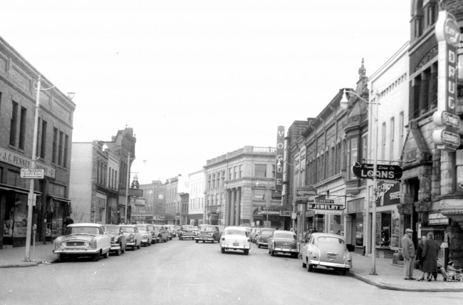 River Street circa 1955 looking east from the Maple Street Intersection cars are parked along both sides of the streets and shoppers are walking the sidewalks