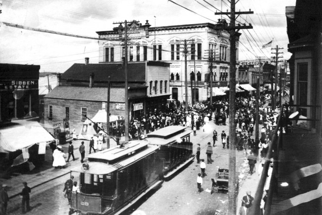 Photo of River Street circa 1900 that shows a busy street with lots of people and a two car trolley in the center of the street