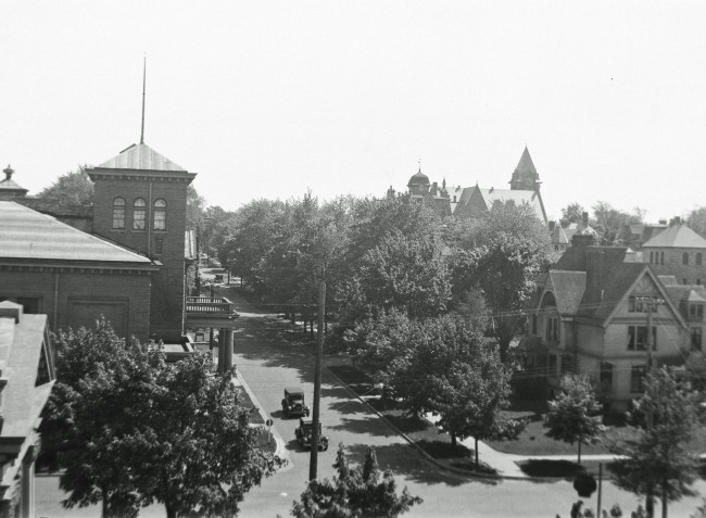 View of Maple Street taken from a roof top that shows cars driving by the Ramsdell Theater and the First Congregational Church in the background