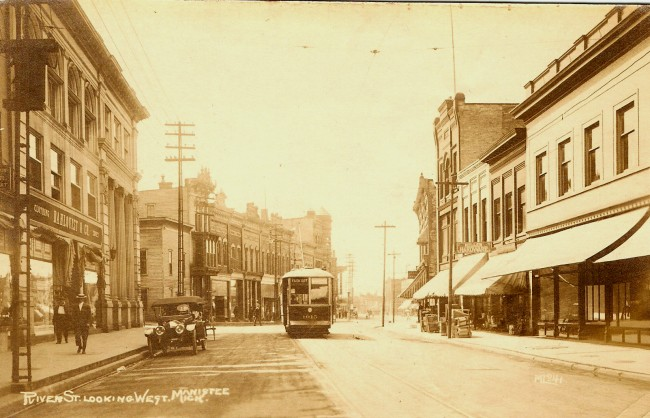 River Street in Downtown Manistee as seen in 1920 that shows a trolley near the Poplar Street intersection