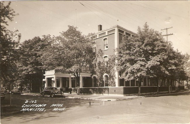 Black and White postcard of the Chippewa Hotel that shows the large three story building  with the entrance on pine street a car is parked on the street with large trees shading the sidewalk