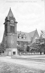 Historical photo of the First Congregational Church in Manistee this large three story brick building with a clock tower is the focus of this photo