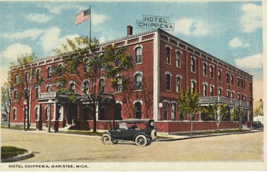 Postcard of the Hotel Chippewa in Manistee Michigan this three story red brick building had two entrances with large columns supporting the marquee a flag is seen flying on the roof