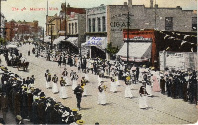 Historical Postcard of a parade on River Street in downtown Manistee people stand on the sidewalks and watch the women in long white skirts and jackets playing in a band followed by a horse drawn carriage
