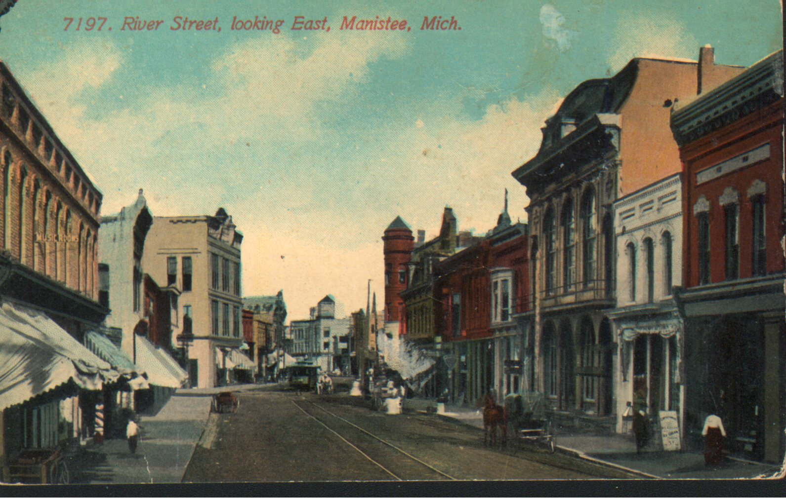 Historical colored postcard of River Street with the tower on the Ramsdell Building being a prominent feature in the background the trolley is near the intersection of River and Maple Street and awnings are pulled down to shade the sun
