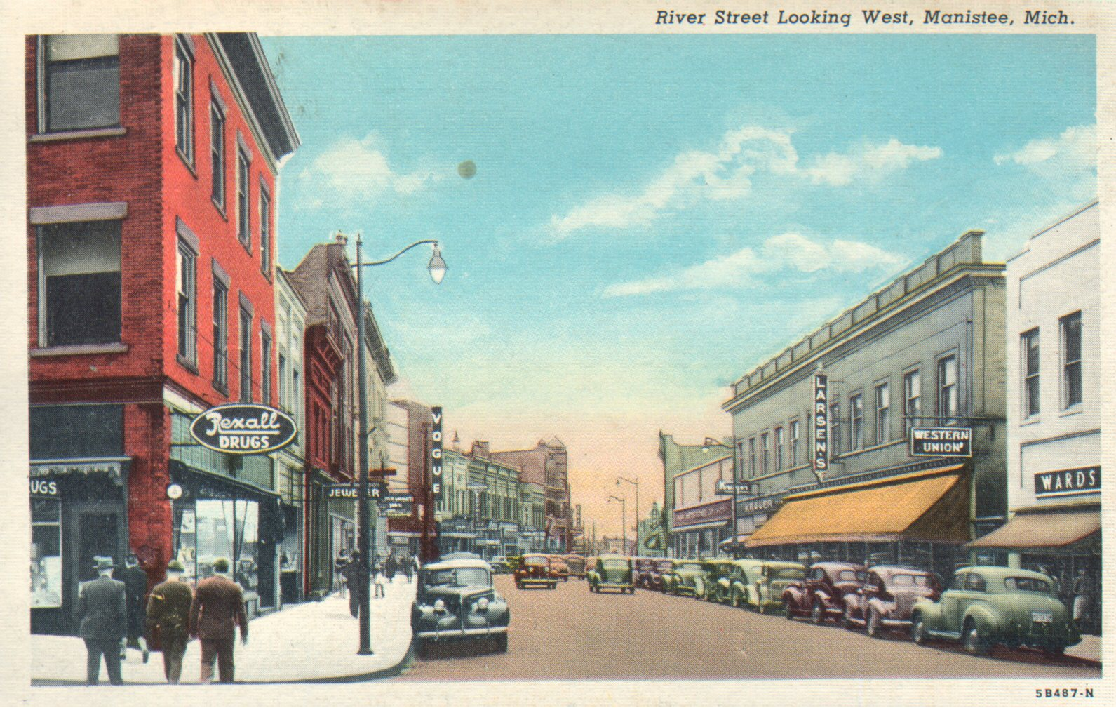 Colored Historical postcard of River Street Looking West in downtown Manistee cars are parked along the street and pedestrians are walking down the sidewalk  signs advertising Rexall Drugs, Larsen's, Kroger and Vogue are highlighted