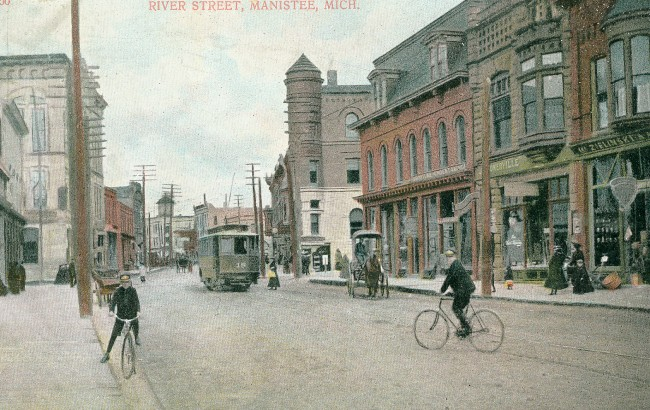Historical Photo of downtown Manistee that shows boys on bikes, horse and buggy and trolley on the street as pedestrians walk the sidewalk of River Street with the beautiful Victorian buildings on each side of the street