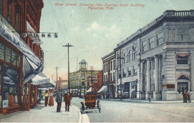 Historical Photo of river Street looking east with the new three story Savings Bank Building in the foreground  a few pedestrians are seen on the street with a carriage parked on the street