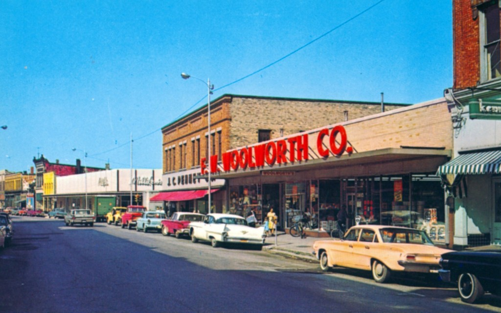 Photo of River Street taken around 1965 with the F.W. Woolworth Co. Building in the foreground and the J.C. Penny and Milliken's building are seen as you look down the street that is lined with cars from the 1960's
