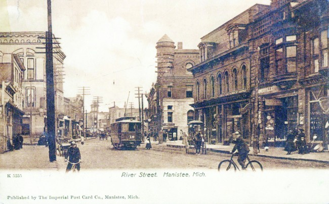 Historical Photo of downtown Manistee looking east towards the Ramsdell Building with boys on bikes, horse and buggies and the trolley on the street as pedestrians are walking down the side walk on River Street