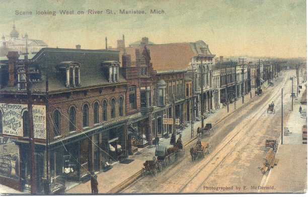 Scene Looking West on River Street with horse drawn carts and wagons on the street that shows trolley rails running down the middle of the street with the Berglund building in the foreground