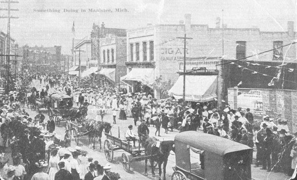 Historical Postcard that reads Something Doing in Manistee that shows horse and buggies lined up on the street with the sidewalks packed with pedestrians