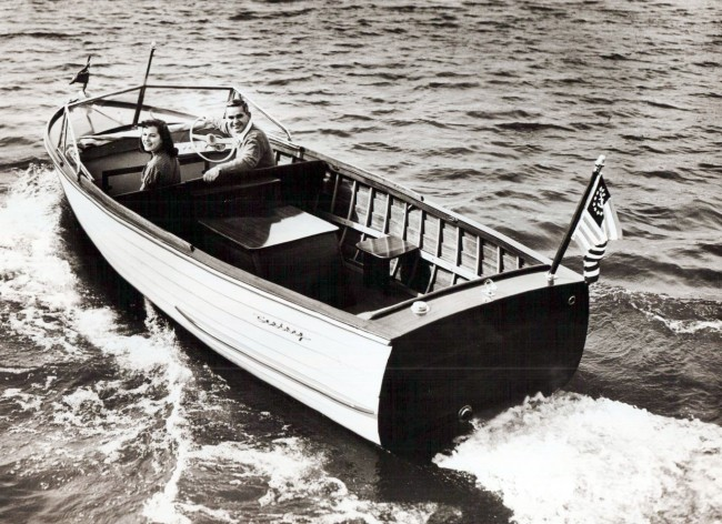 Old photo of a man and woman in a wooden Century Viking these wooden boats were manufactured in Manistee Michigan