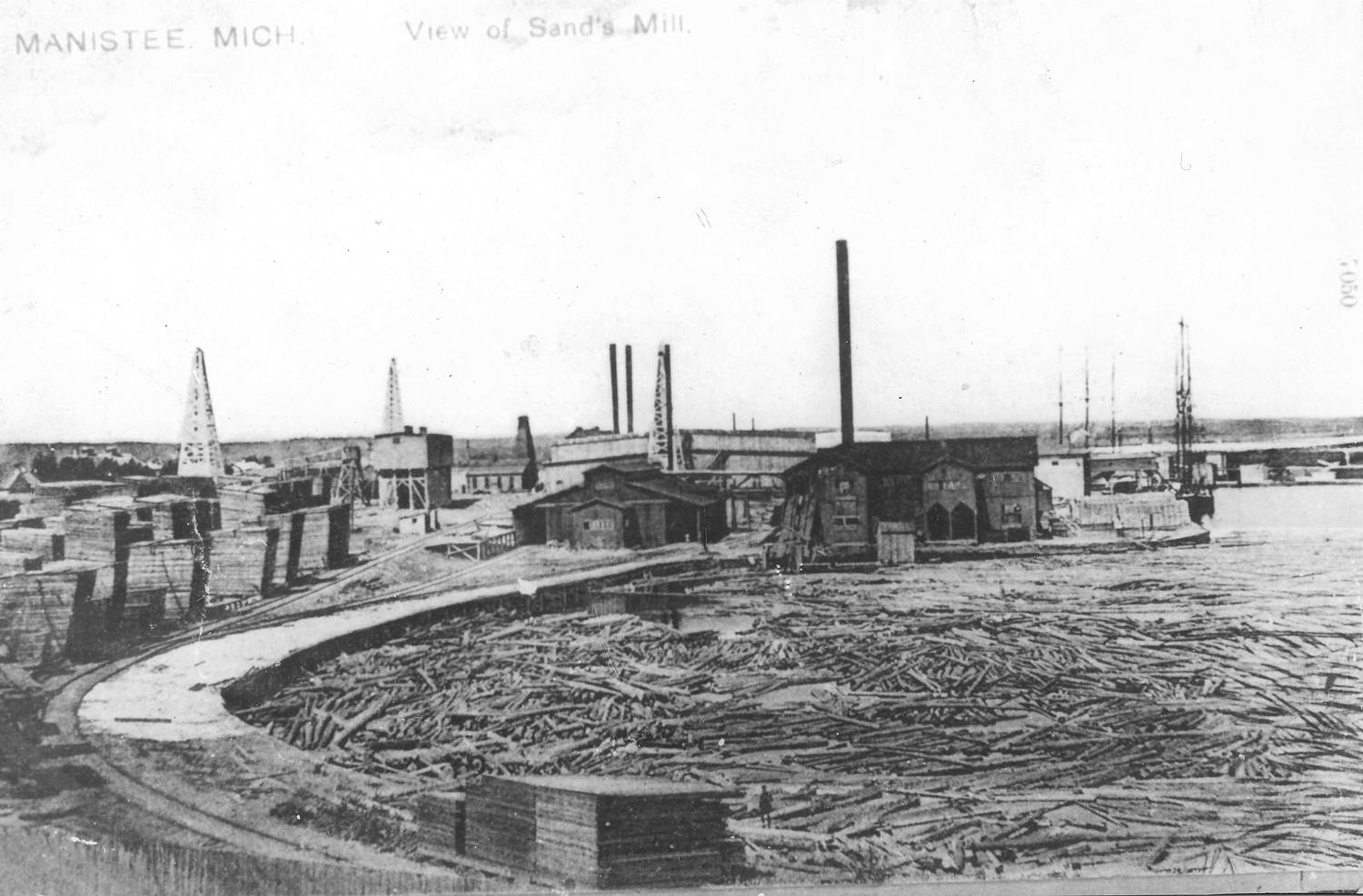 Historical Photo of the Lumber Mills as seen on Manistee Lake with logs in the water and buildings all around